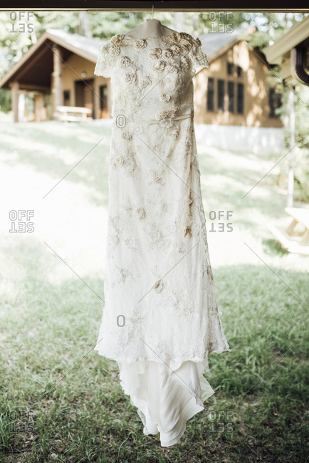 White dress hanging on wood over grassy field at yard