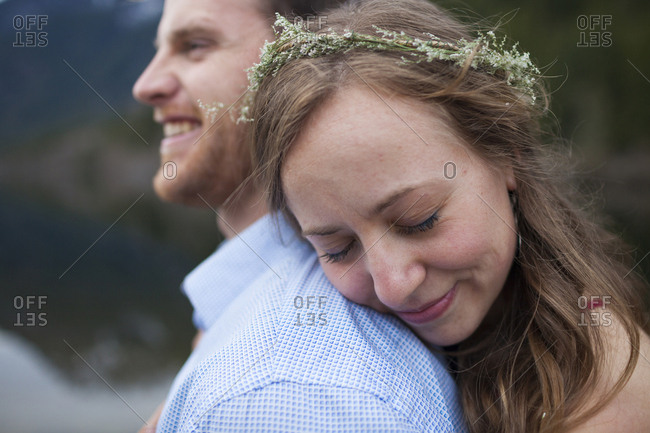 Girlfriend with eyes closed wearing wreath while embracing boyfriend at lakeshore