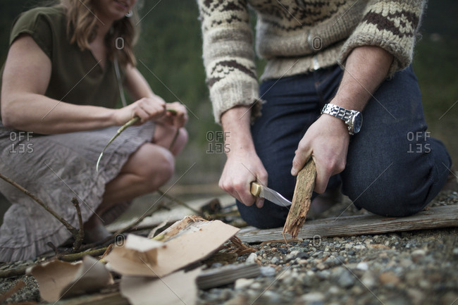 Midsection of boyfriend cutting wood while kneeling by girlfriend at campsite