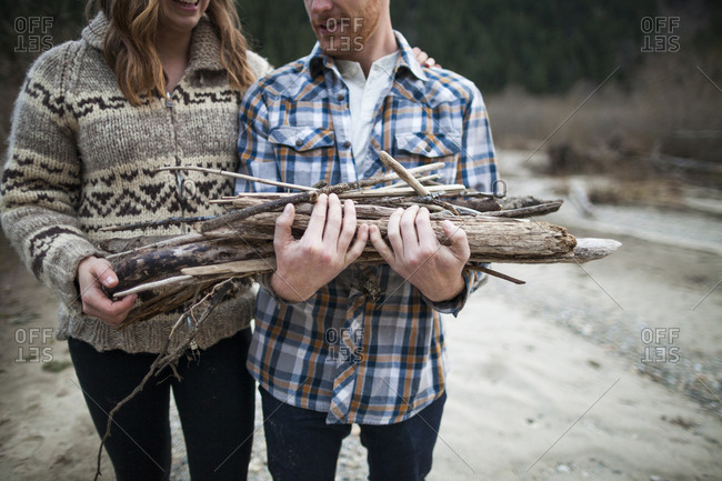 Midsection of boyfriend holding firewood while standing beside girlfriend at campsite