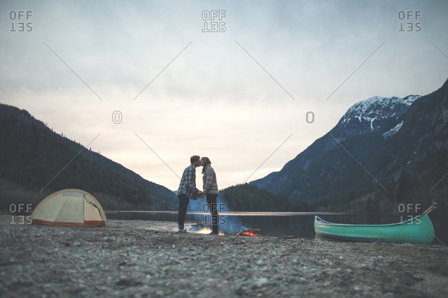 Full length of young couple holding hands while kissing at lakeshore against mountains during dusk