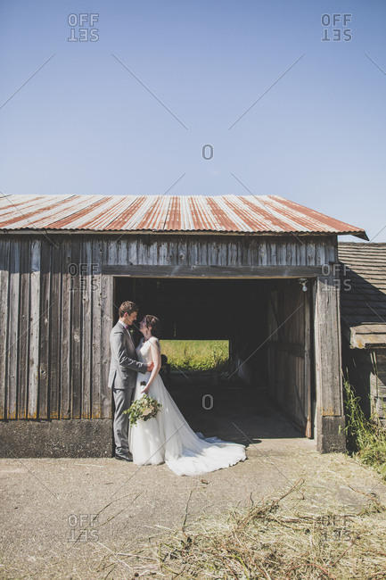 Groom embracing bride while standing by barn against clear sky during summer