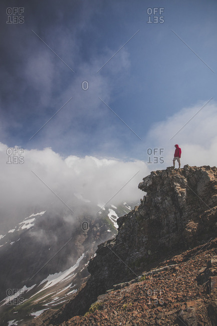 Side view of man standing on cliff against cloudy sky