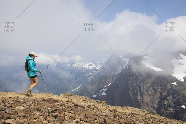 Side view of female hiker with hiking pole walking on mountain against cloudy sky
