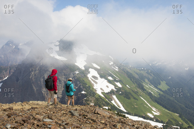 Rear view of hikers looking at view while standing on mountain against cloudy sky