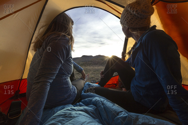 Female friends looking at view while sitting in tent