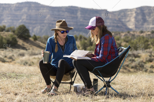 Female friends looking at book while sitting on camping chairs at field against mountains during sunny day