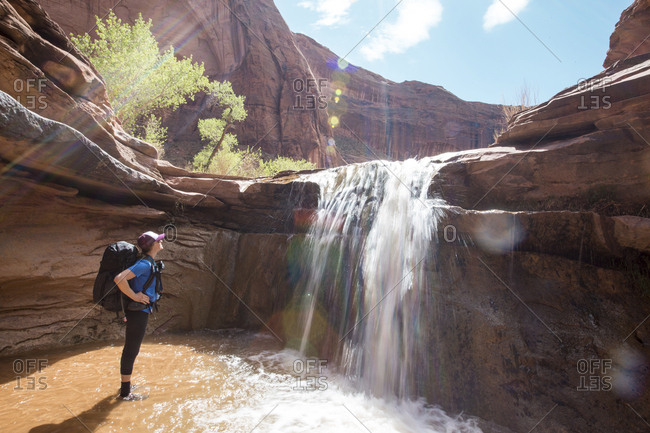 Side view of woman with backpack looking at waterfall against rock formations during sunny day