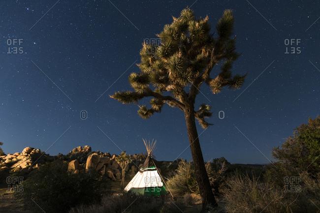 Illuminated Teepee at Joshua Tree National Park against star field