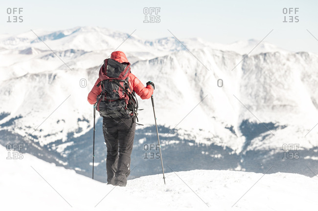 Rear view of female hiker with backpack holding hiking poles while standing against snowcapped mountains