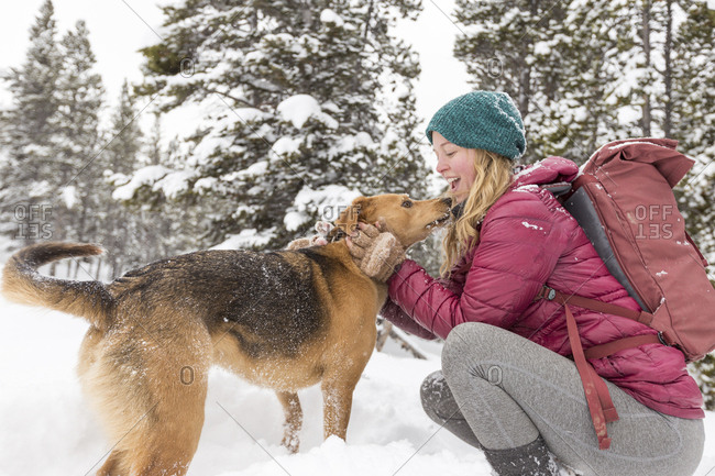 Side view of happy woman with backpack petting dog while crouching on snowy field