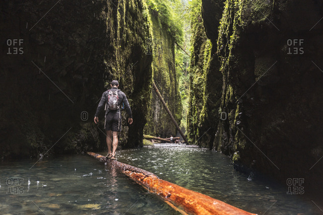 Rear view of hiker with backpack walking on wood at Oneonta Gorge