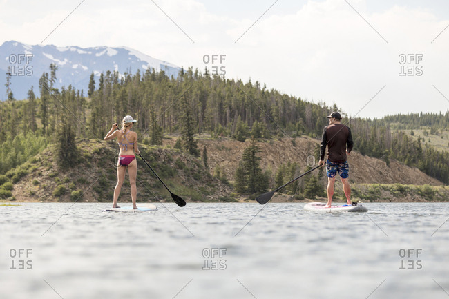 Rear view of friends paddle boarding on lake against mountains