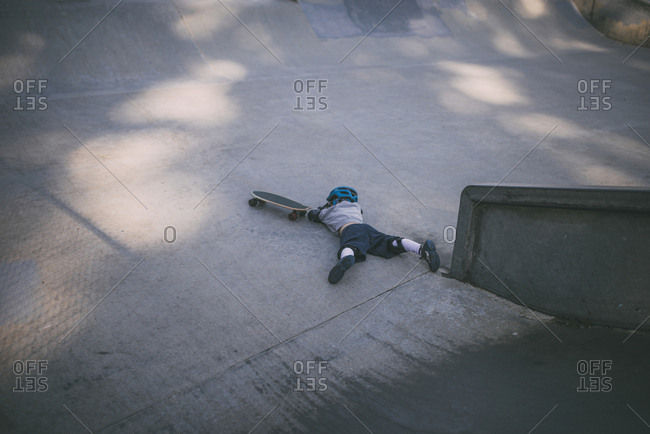 High angle view of boy falling from skateboard at park