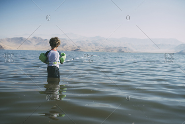 Rear view of boy fishing while standing in river against clear sky during sunny day
