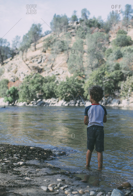 Rear view of boy fishing while standing in lake against mountains