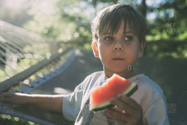 Boy eating watermelon against hammock during sunny day