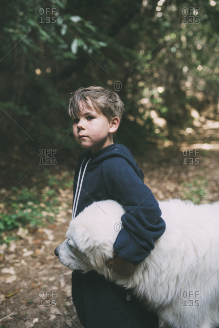 Thoughtful boy embracing dog while standing at park
