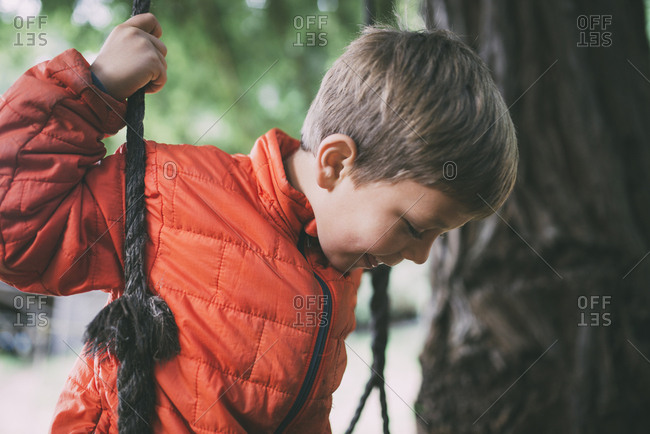 Carefree boy playing on rope swing at park