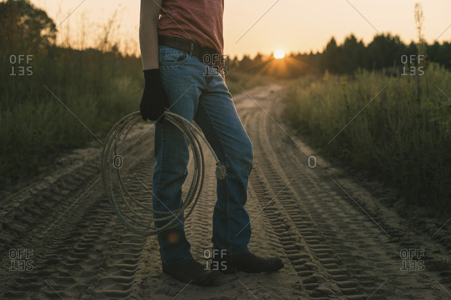 Low section of boy holding rope while standing on dirt road during sunset