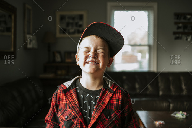 Playful boy with eyes closed wearing cap at home