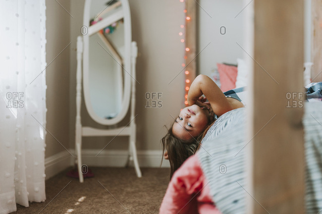 Portrait of girl lying on bed at home