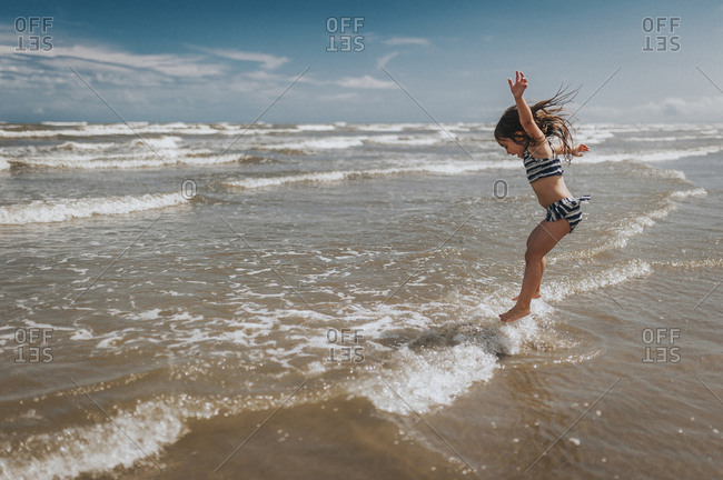 Carefree girl jumping in waves on shore at beach against sky