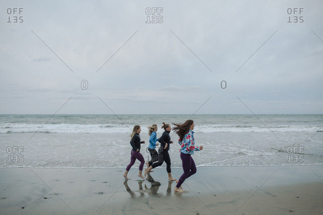 Female friends jogging while exercising at beach against sky