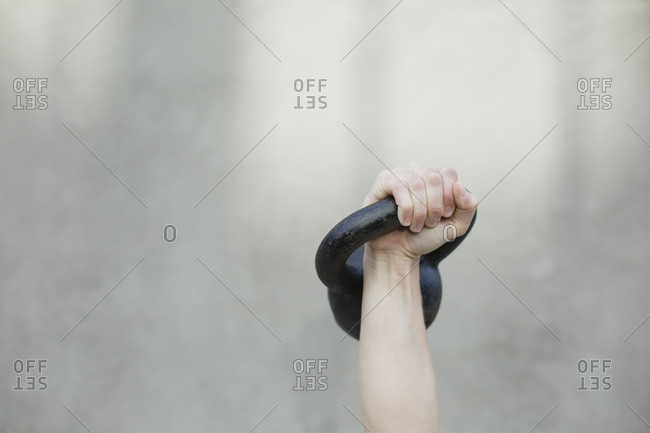 Cropped hand of woman lifting kettlebell against wall while exercising