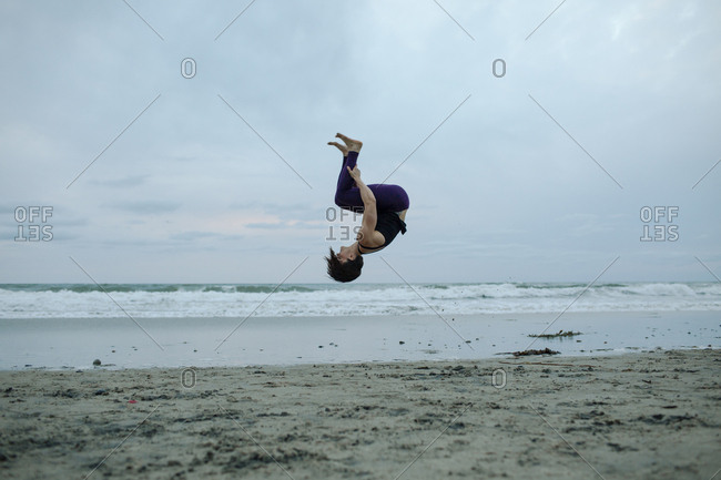 Carefree woman back flipping at beach while exercising against sky