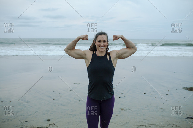 Portrait of confident muscular build woman flexing muscles at beach