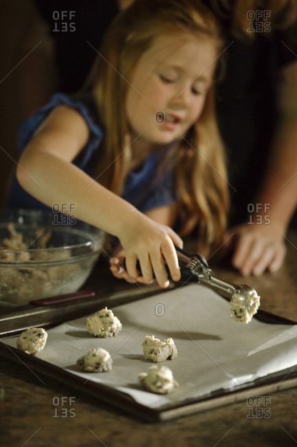 Girl putting cookie dough on baking sheet using serving scoop at home