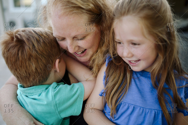 Close-up of happy mother embracing children