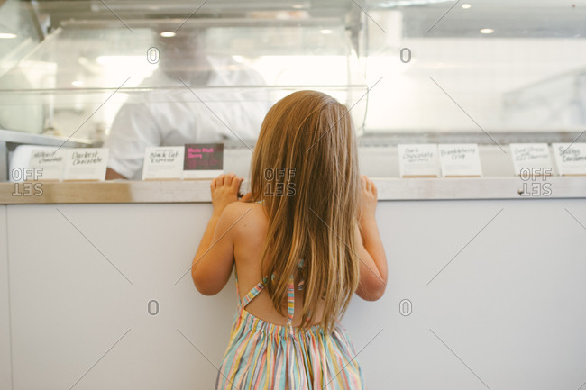 Rear view of little girl picking out a flavor at an ice cream shop