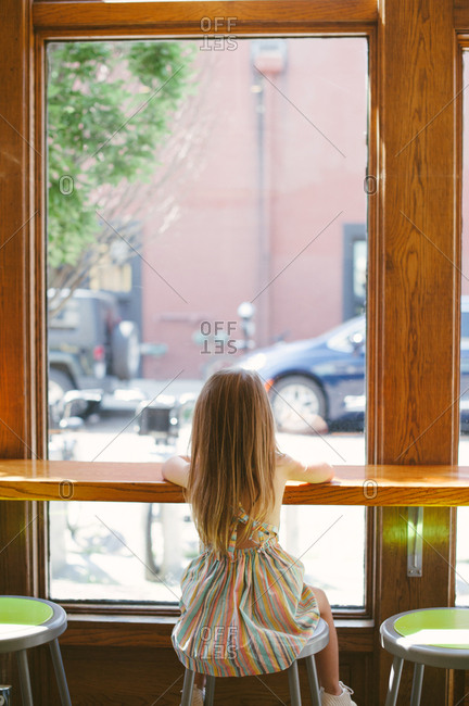 Little girl sitting on stool looking out window
