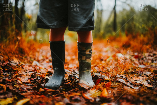 Child standing in fallen leaves wearing mismatched rubber boots