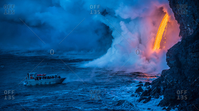 Hawaii Volcanoes National Park, Hawaii, USA. - January 25, 2017: A ship passes to view lava falling to create an explosion from the heat and pressure at the water.