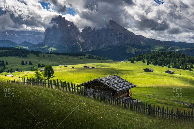 Chalets and wooden fence in field in the Dolomites region in South Tryol, Italy