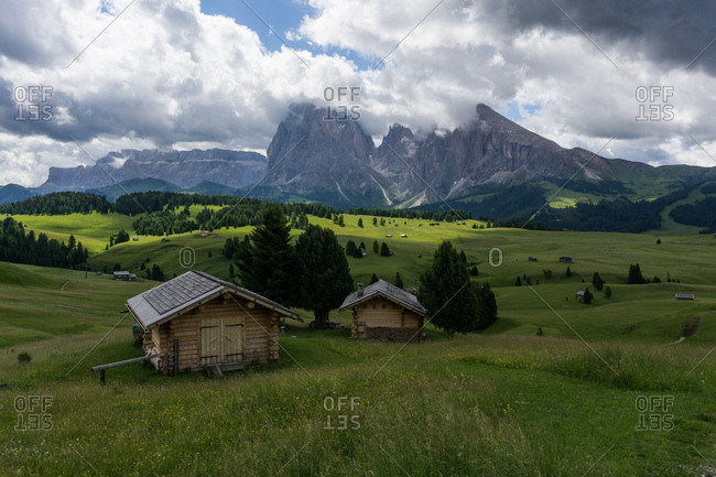 Log chalets in a field in the Dolomites region in South Tryol, Italy