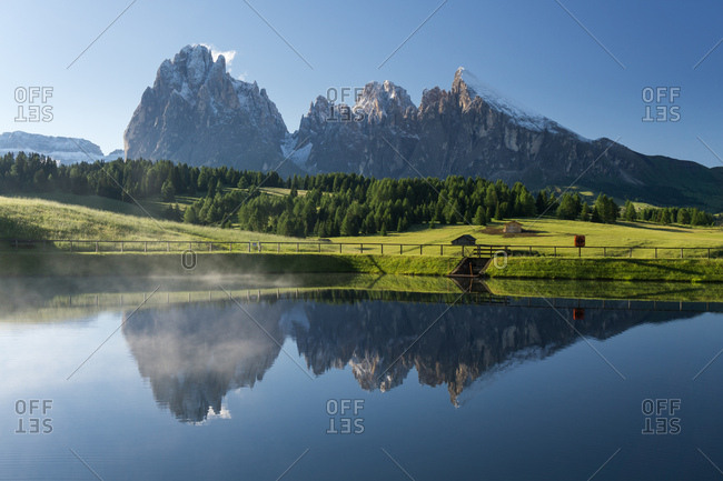 The Dolomites mountain range reflecting in a lake in South Tryol, Italy