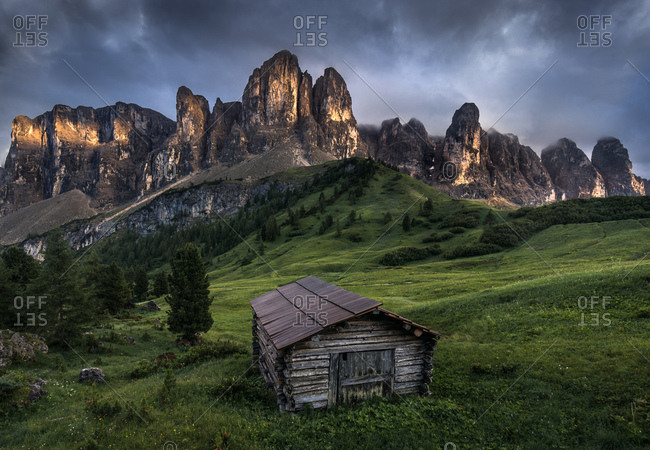 Dark clouds over Gardena Pass and chalet in the Dolomites region in South Tyrol, Italy
