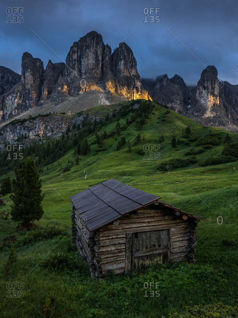 Dark sky over Gardena Pass and chalet in the Dolomites region in South Tyrol, Italy