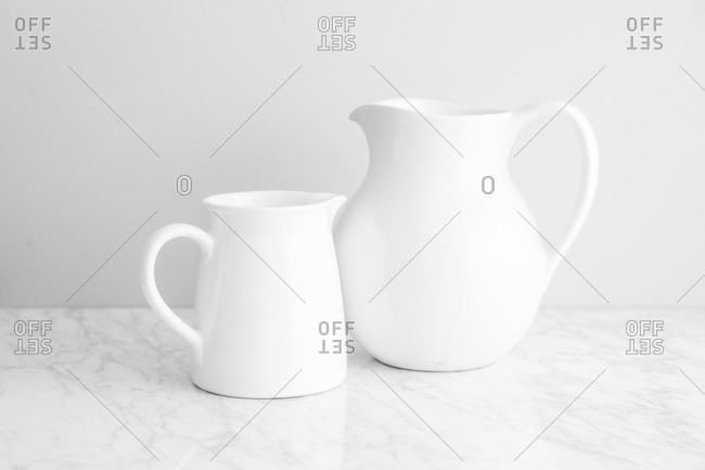 Two white pitchers on a marble counter