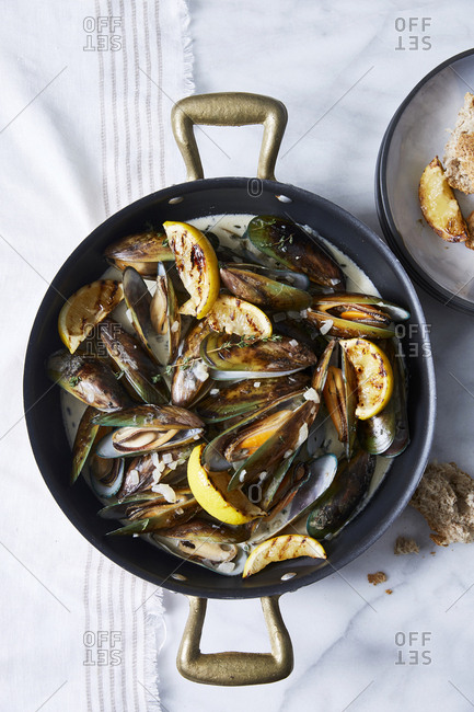 Seafood brunch of mussels in a shallot cream sauce and lemon wedges served with crusty bread