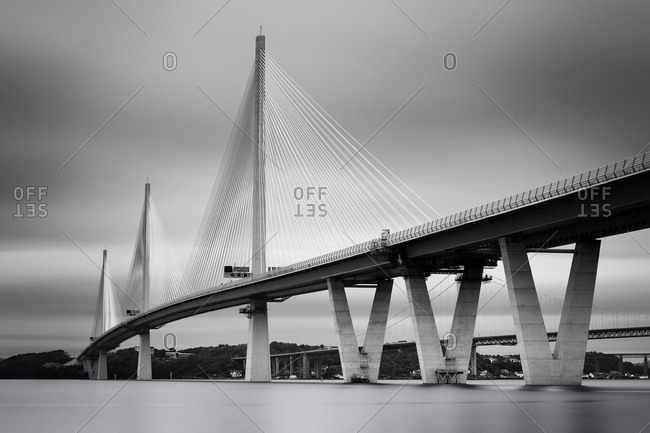 A black and white long exposure of the new Queensferry crossing bridge over the Firth of Forth estuary, South Queensferry, Edinburgh