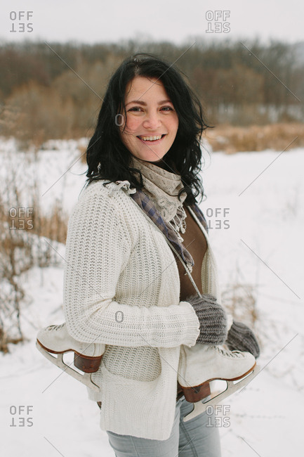 Smiling woman with a pair of ice skates over a shoulder and windswept hair
