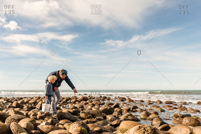 Father and son exploring rocky coast