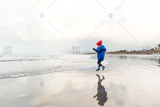 Boy skips on beach with rainbow