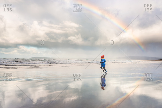 Boy runs on beach with rainbow