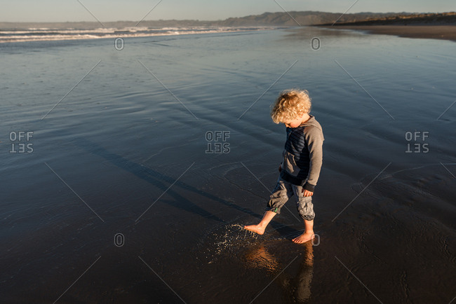 Boy playing in wet sand
